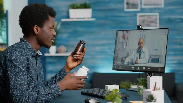 Homem afro-americano em videoconferência com seu médico, usando o aplicativo médico da internet para a área de saúde.