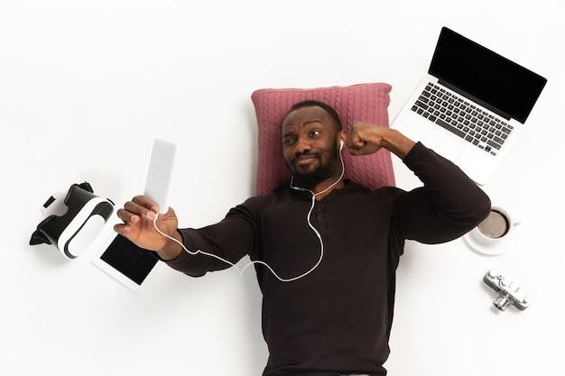 Homem afro-americano emocional usando telefone rodeado por gadgets isolados na parede branca do estúdio.