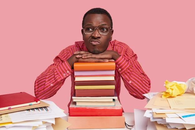 Homem afro-americano entediado e infeliz tem exoressão facial, franze os lábios, tem expressão pensativa, pensa em um novo plano inovador