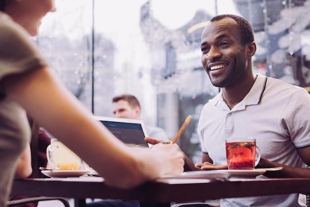 Homem afro-americano entusiasmado e atraente sorrindo enquanto olha para o colega e fala