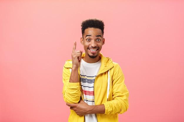 Homem afro-americano entusiasmado e satisfeito, adicionando a sugestão, levantando o dedo indicador em um gesto de eureka e sorrindo alegremente enquanto discute uma invenção ou teoria interessante, sorrindo amplamente sobre a parede rosa