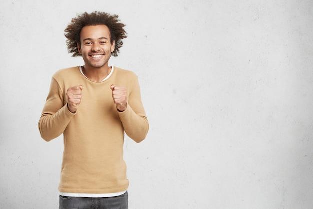 Homem afro-americano esperançoso mantém as mãos em punhos, sorri feliz enquanto espera por uma decisão importante