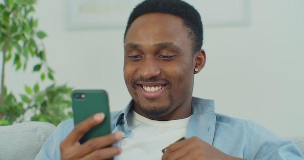 Homem afro-americano está fazendo compras online, pagando com cartão do banco e smartphone em casa usando opções de pagamento modernas