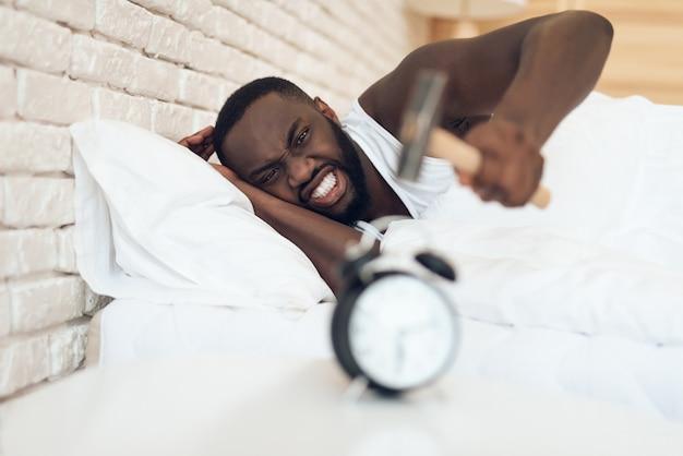 Homem afro-americano está martelando despertador. acordar.