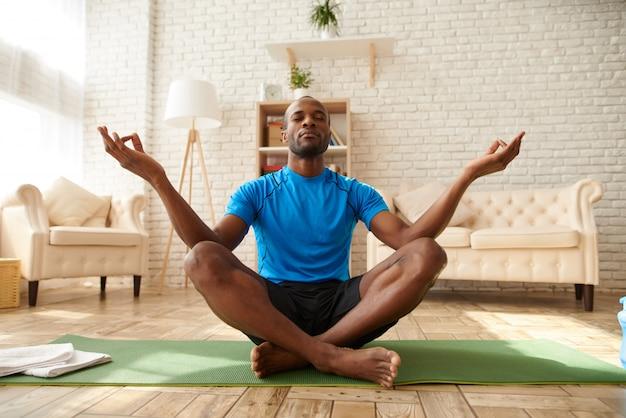 Homem afro-americano está meditando em lótus.
