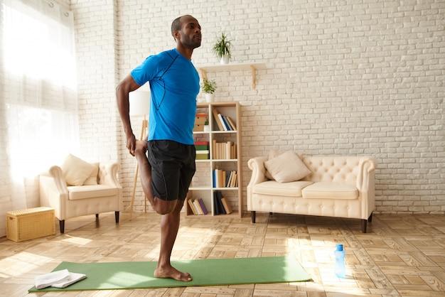 Homem afro-americano está praticando ioga em casa.