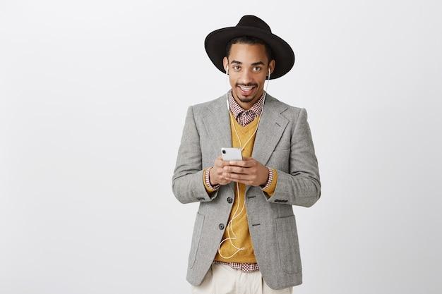 Homem afro-americano estiloso de terno usando smartphone e ouvindo música em fones de ouvido