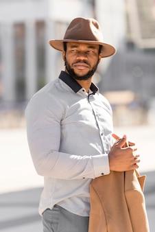 Homem afro-americano estiloso posando olhando para longe