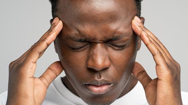 Homem afro-americano exausto e chateado, sentindo dores, sofrendo de enxaqueca, massageando as têmporas estúdio