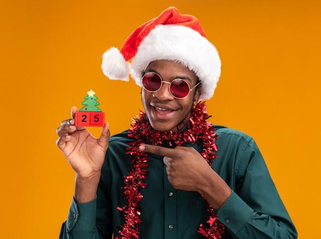Homem afro-americano feliz com chapéu de papai noel com guirlanda usando óculos escuros segurando cubos de brinquedo com data 25 apontando com o dedo indicador em pé sobre a parede laranja