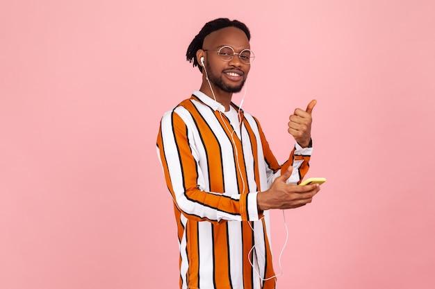 Homem afro-americano feliz com fones de ouvido mostrando os polegares usando um aplicativo móvel para ouvir música