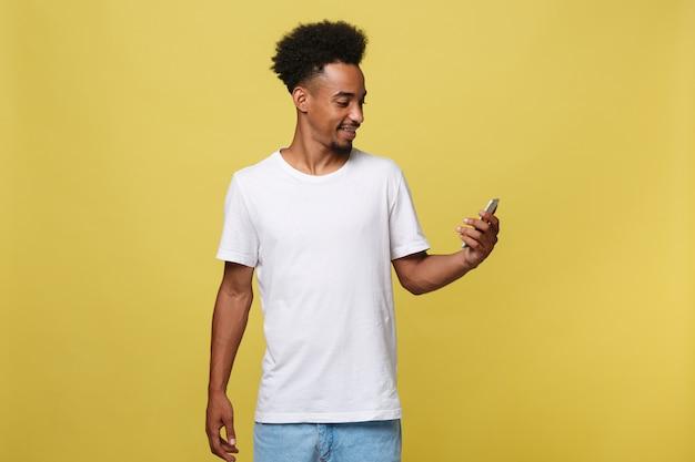 Homem afro-americano feliz com sorriso e telefone celular de utilização.