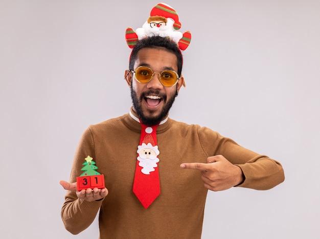 Homem afro-americano feliz com suéter marrom e aro de papai noel