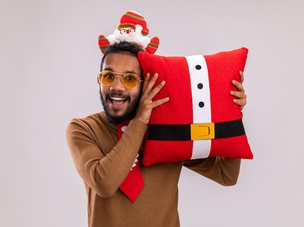 Homem afro-americano feliz com suéter marrom e papai noel na cabeça com gravata vermelha engraçada segurando a almofada de natal, olhando para a câmera com um sorriso no rosto em pé sobre um fundo branco