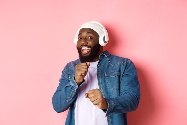 Homem afro-americano feliz dançando, ouvindo música em fones de ouvido e olhando para a câmera, em pé sobre um fundo rosa