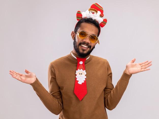 Homem afro-americano feliz, de suéter marrom e papai noel na cabeça com gravata vermelha engraçada, segurando o bastão de doces, olhando para a câmera, sorrindo, abrindo os braços para os lados, de pé sobre um fundo branco