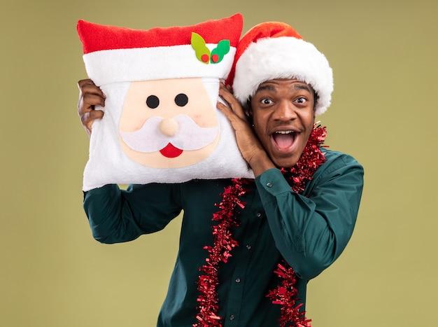 Homem afro-americano feliz e animado com chapéu de papai noel com festão segurando a almofada de natal, olhando para a câmera em pé sobre fundo verde.