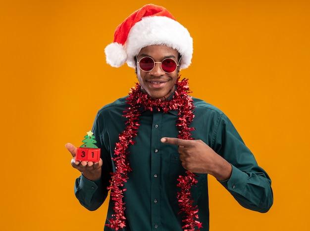 Homem afro-americano feliz e positivo com chapéu de papai noel com festão usando óculos escuros segurando cubos de brinquedo com a data de ano novo apontando com o dedo indicador em pé sobre fundo laranja