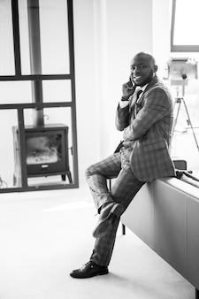 Homem afro-americano feliz e satisfeito empresário sorrindo e olhando para a câmera em apartamento loft.