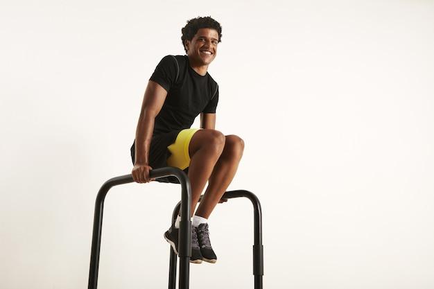 Homem afro-americano feliz e sorridente com roupa de treino sintética preta, fazendo exercícios em casa nas barras paralelas, isolado no branco