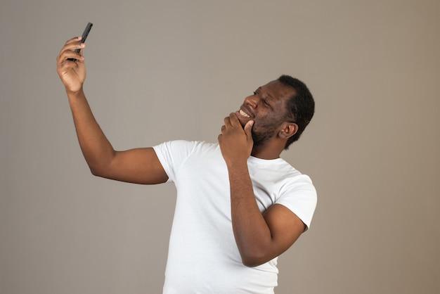 Homem afro-americano feliz e sorridente tomando selfie com a mão no queixo, em frente à parede cinza.