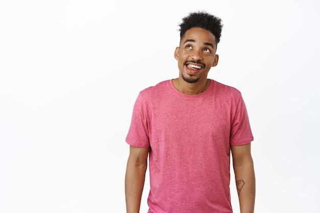 Homem afro-americano feliz sorrindo pensativo, olhando para o canto superior esquerdo e imaginando smth saboroso, sonhando com uma coisa deliciosa, em pé na camiseta rosa em branco.