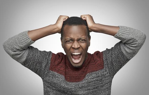 Homem afro-americano furioso gritando e segurando a cabeça com as mãos e arrancando os cabelos