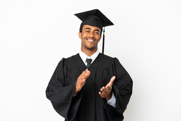 Homem afro-americano graduado em universidade sobre fundo branco isolado aplaudindo após apresentação em conferência