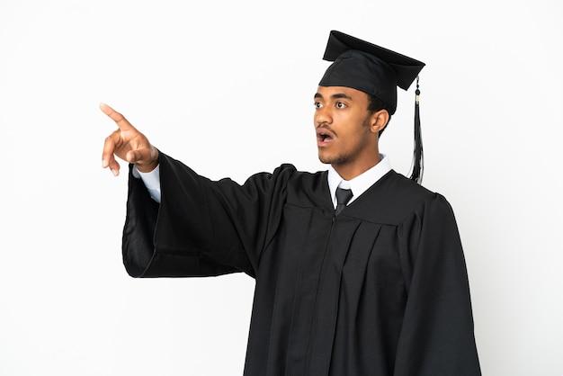 Homem afro-americano graduado em universidade sobre fundo branco isolado apontando para longe