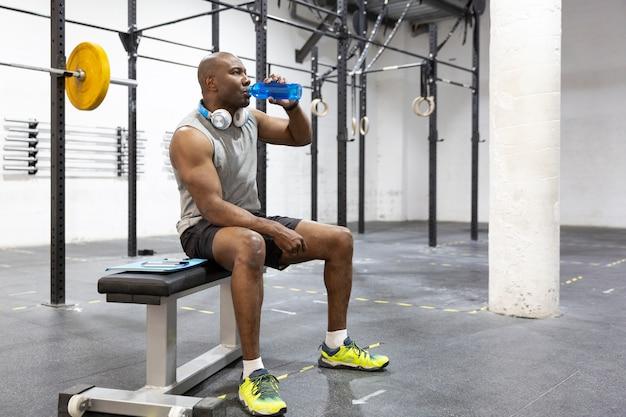 Homem afro-americano, hidratando-se após o exercício no centro de fitness. espaço para texto.