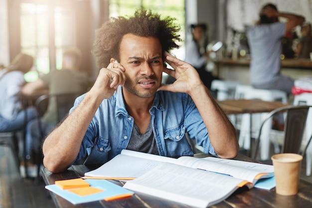 Homem afro-americano hippie de pele escura com cabelo escuro encaracolado, vestindo uma camisa jeans, sentado em uma cafeteria barulhenta tentando ouvir a voz no smartphone com conexão ruim