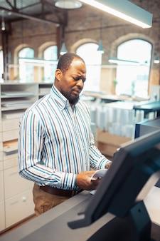 Homem afro-americano. homem maduro afro-americano de camisa listrada, trabalhando em uma editora