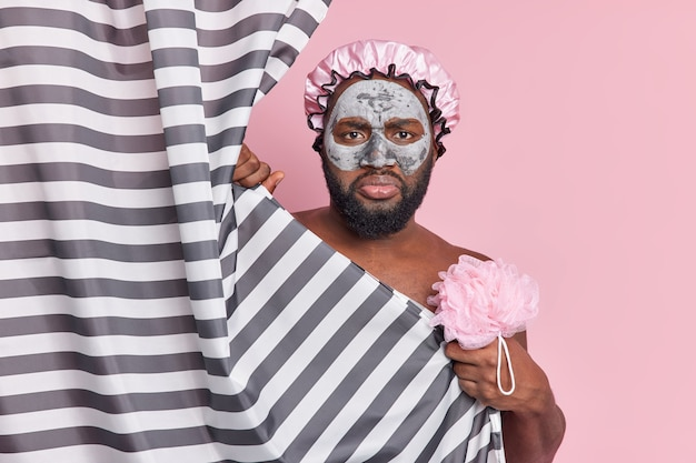 Homem afro-americano insatisfeito com pele escura e fresca cuida do corpo e a pele toma banho regularmente segure esponja de banho aplica máscara de argila em poses de rosto atrás de uma cortina listrada