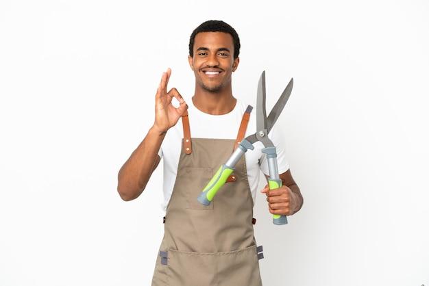 Homem afro-americano, jardineiro, segurando uma tesoura de poda sobre um fundo branco isolado, mostrando um sinal de ok com os dedos