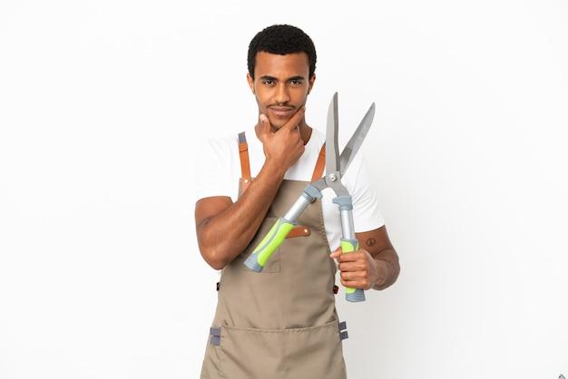 Homem afro-americano, jardineiro, segurando uma tesoura de poda sobre um fundo branco isolado, pensando