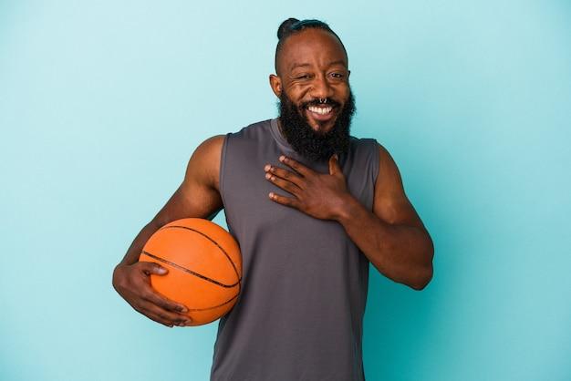 Homem afro-americano jogando basquete isolado em um fundo azul, ri alto, mantendo a mão no peito.