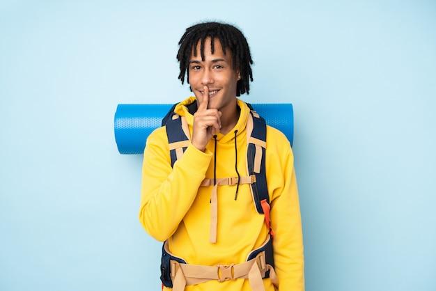 Homem afro-americano jovem alpinista com uma mochila grande em uma parede azul, fazendo o gesto de silêncio