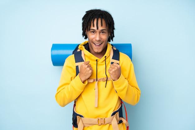 Homem afro-americano jovem alpinista com uma mochila grande isolada em um azul comemorando uma vitória