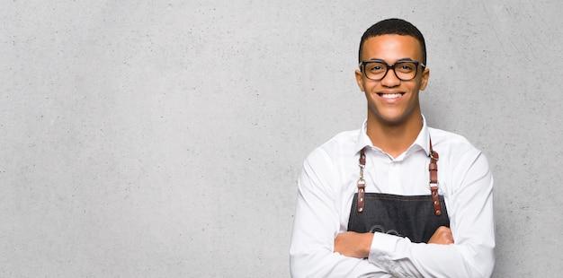 Homem afro-americano jovem barbeiro com óculos e feliz na parede texturizada