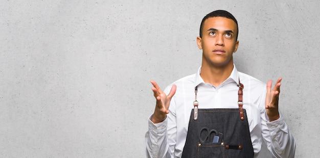 Homem afro-americano jovem barbeiro frustrado por uma situação ruim na parede texturizada
