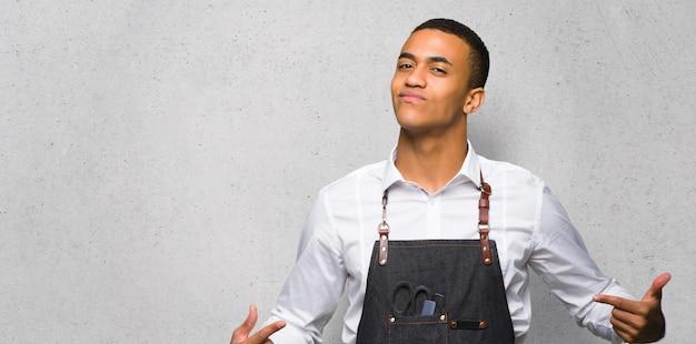 Homem afro-americano jovem barbeiro orgulhoso e satisfeito em amor-se conceito na parede texturizada