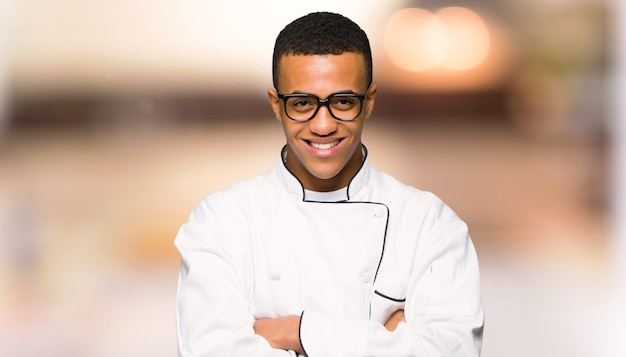 Homem afro americano jovem chef com óculos e feliz em fundo desfocado