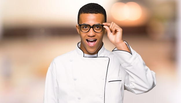 Homem afro americano jovem chef com óculos e surpreso em fundo desfocado