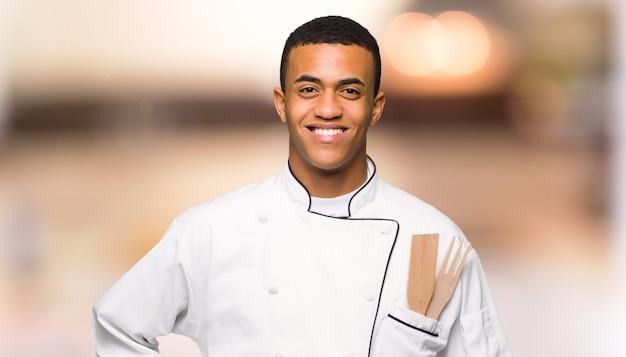 Homem afro americano jovem chef posando com os braços no quadril e sorrindo em fundo desfocado