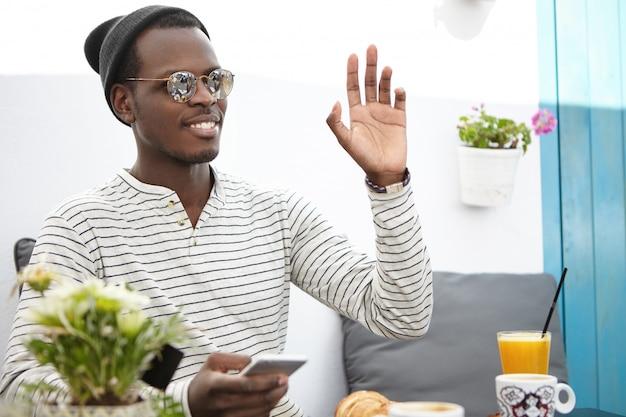 Homem afro-americano jovem de aparência amigável alegre, usando chapéus e óculos de sol da moda, levantando a mão e gesticulando enquanto chamava o garçom durante o café da manhã no restaurante, usando o dispositivo eletrônico