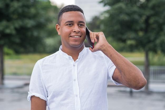 Homem afro-americano jovem e feliz falando ao celular