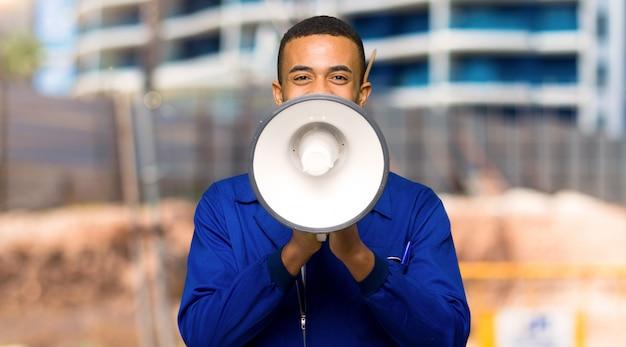 Homem afro americano jovem trabalhador gritando através de um megafone para anunciar algo em um canteiro de obras