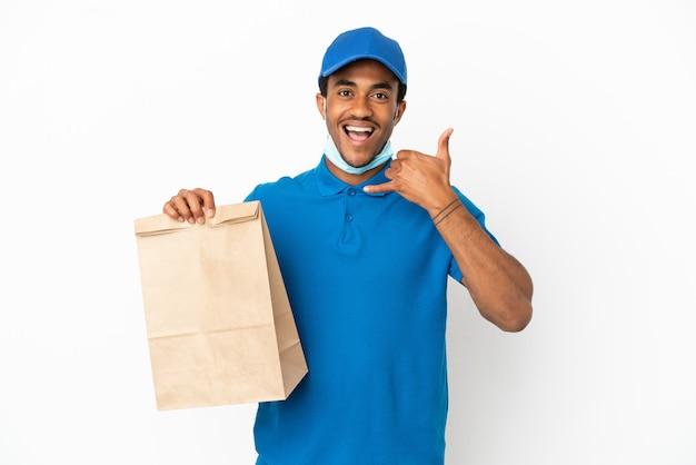 Homem afro-americano, levando um saco de comida para viagem, isolado no fundo branco, fazendo gesto de telefone. ligue-me de volta sinal