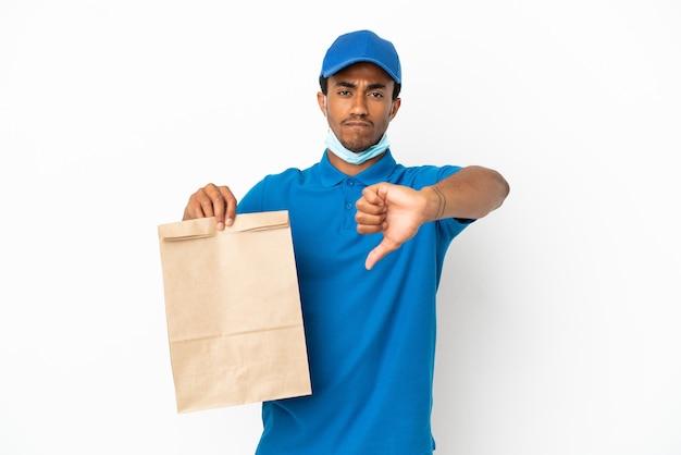 Homem afro-americano levando uma sacola de comida para viagem isolada no fundo branco, mostrando o polegar para baixo com expressão negativa