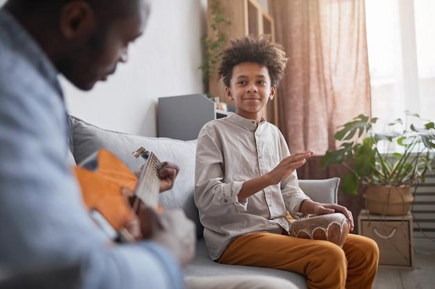 Homem afro-americano maduro e seu filho adolescente passando ótimos momentos juntos em casa tocando guitarra e djembe